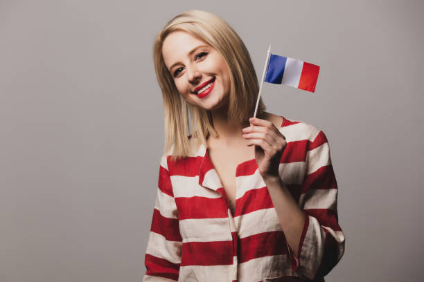 girl holds french flag on gray background stock photo