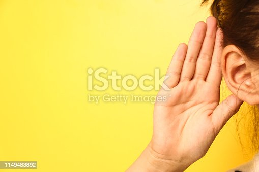 Girl holds her hand near ear and listens carefully isolated on wall background