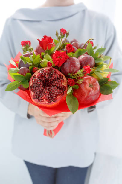 Girl holds in hands an original fruit bouquet consisting of apples, plums, pears, pomegranates and flowers of scarlet roses stock photo