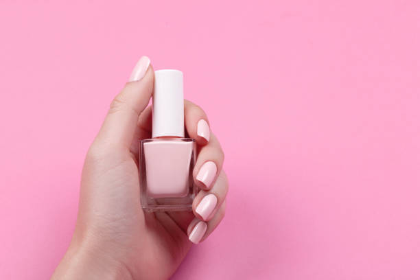 girl holds nail polish with a beautiful manicure - enamel stock photos and pictures