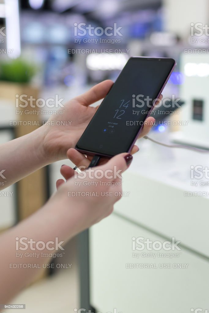 Girl Holds New Samsung Galaxy S9 In Store Against Blurry