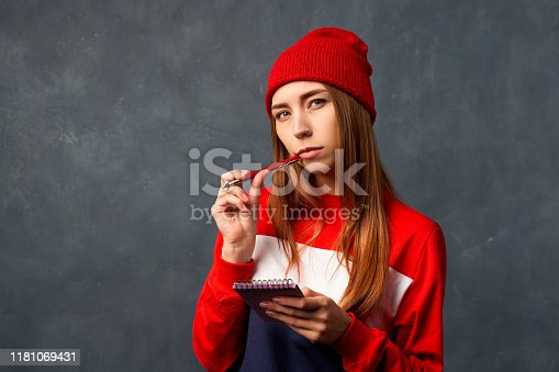 1174436608 istock photo girl holds notepad, pen isolated on textured wall 1181069431