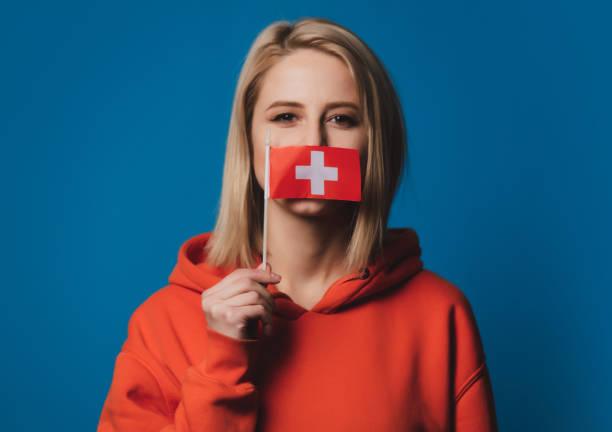 girl holds Switzerland flag on blue background stock photo