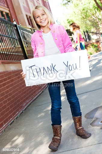 istock Girl holds 'thank you' sign outside of school 539002916