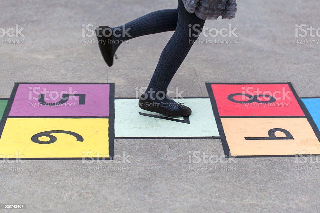 Girl hopscotching stock photo