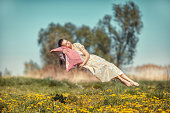 Girl hovers and sleeps on a pillow over a beautiful meadow.