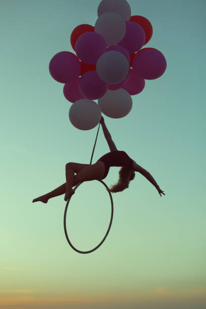 girl hovers in the air on balloons. - equilibrista foto e immagini stock