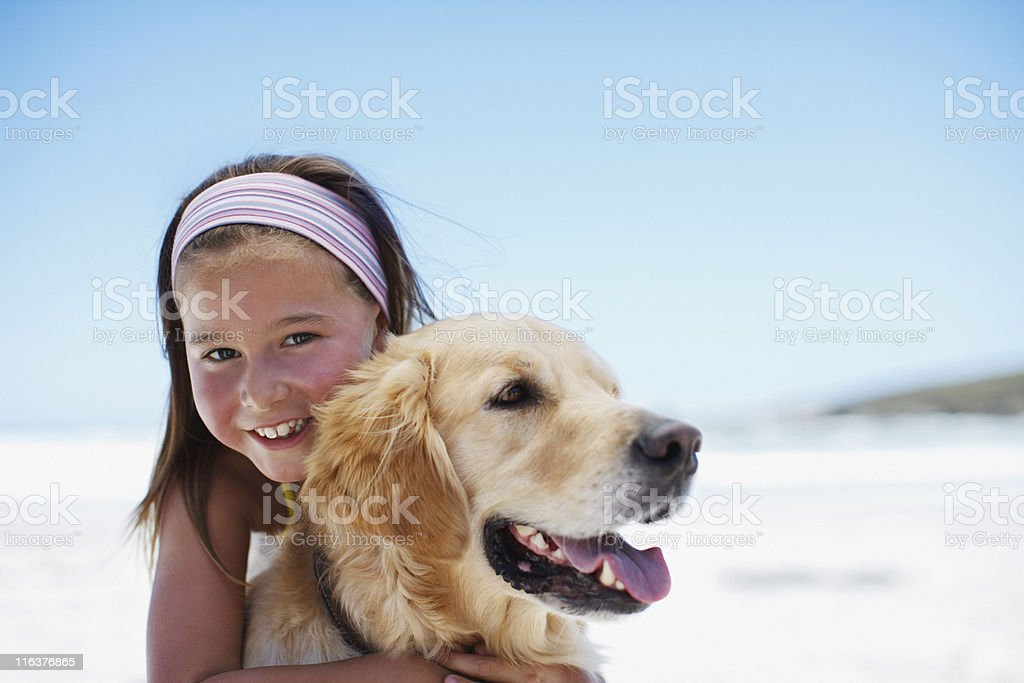 Girl hugging dog on beach stock photo