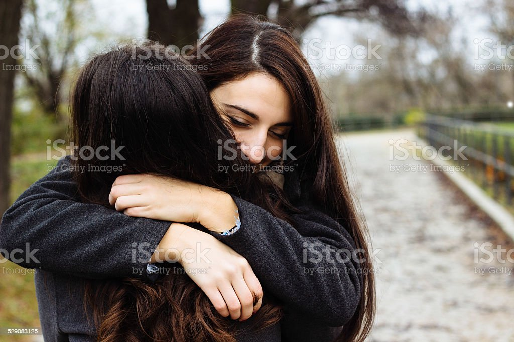 Girl hugging her best friend stock photo