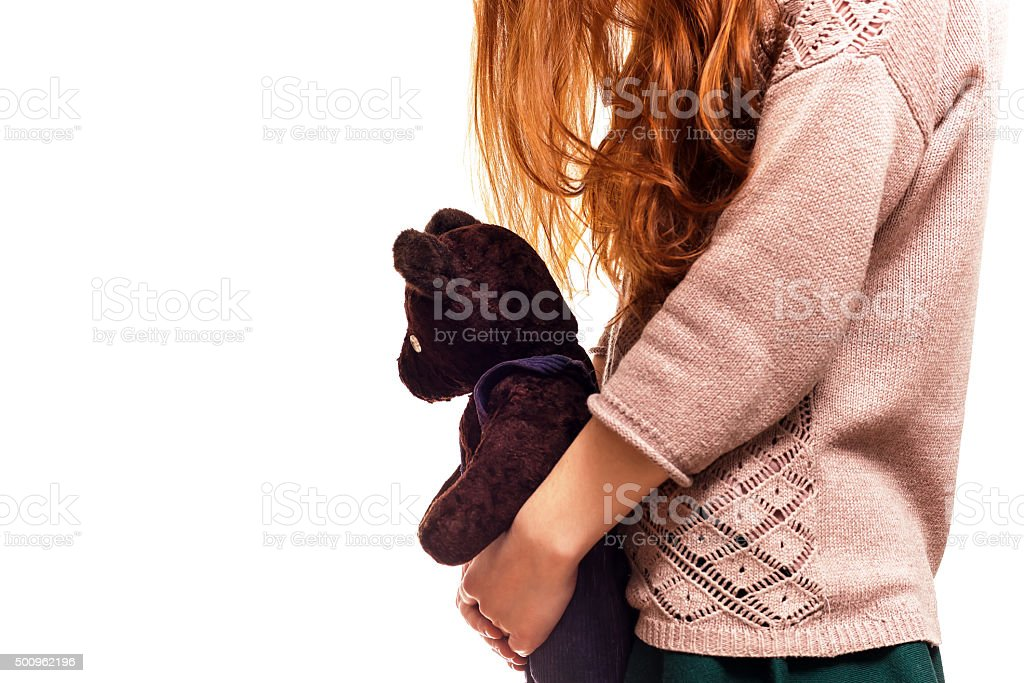 Girl hugging her favorite teddy bear stock photo