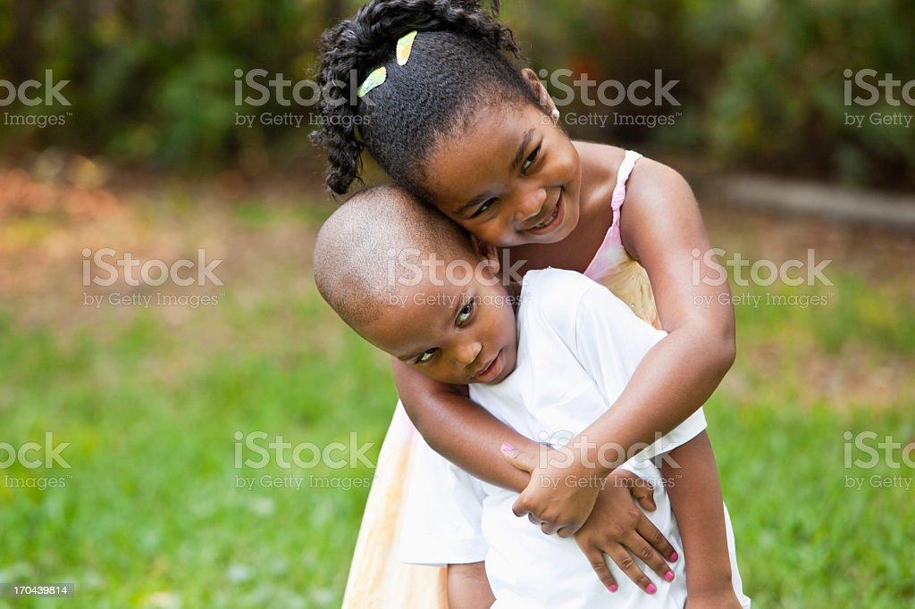 Girl hugging little brother stock photo