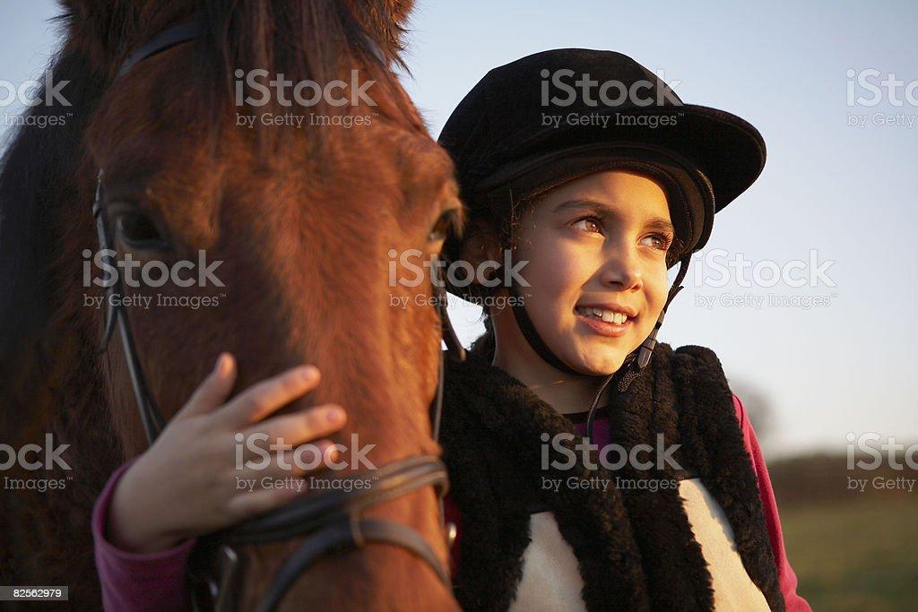 Girl hugging pony stock photo