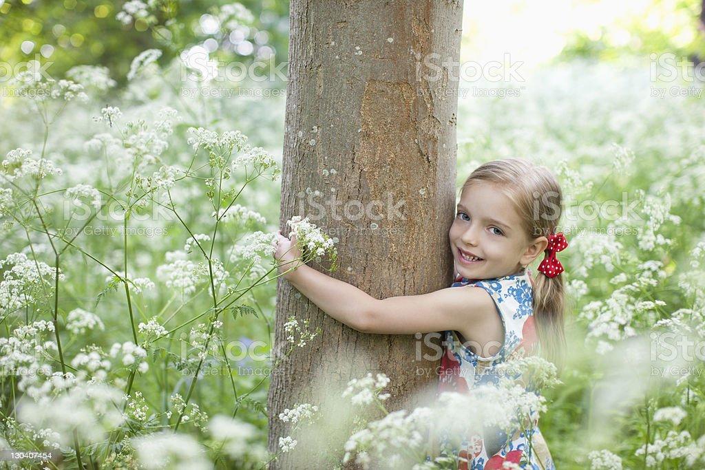 Girl hugging tree in field of flowers royalty-free stock photo