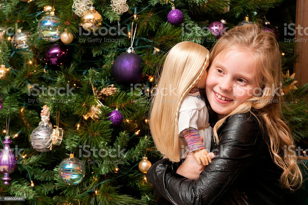 Girl hugs doll at Christmas stock photo
