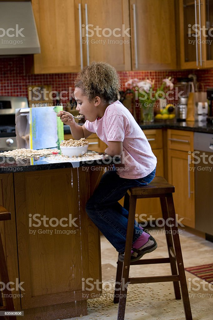 Girl ieating cereal, milk spilling off counter royalty-free stock photo