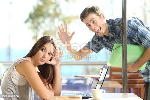 istock Girl ignoring a stalker man waving 536667176