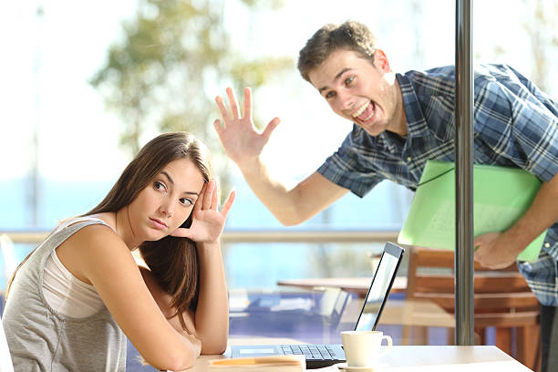 Girl ignoring a stalker man waving Girl ignoring and rejecting to a stalker man waving her in a coffee shop in a blind date bad date stock pictures, royalty-free photos & images