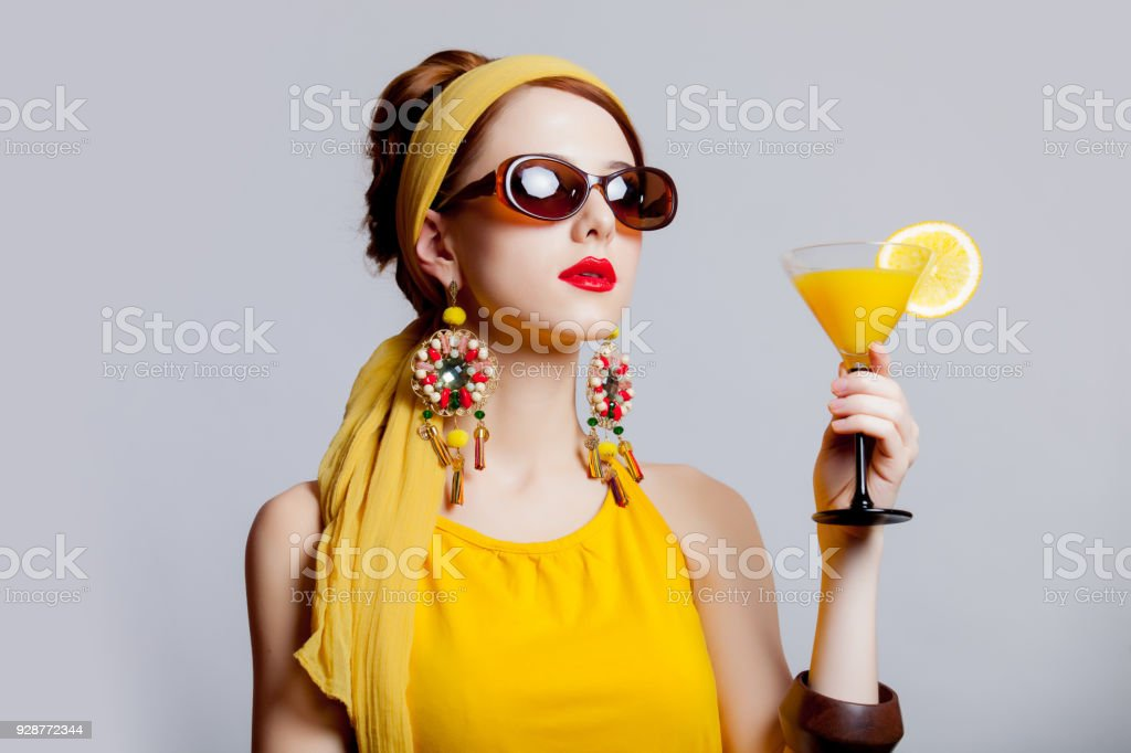 girl in 70s clothes style with tropical cocktail stock photo