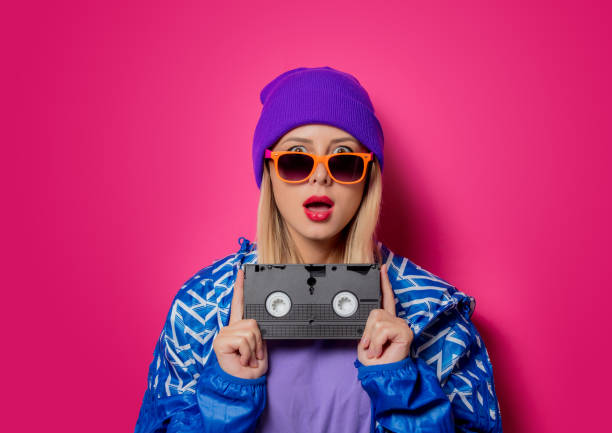 girl in 90s sports jacket and vhs cassette - 1990s style stock photos and pictures