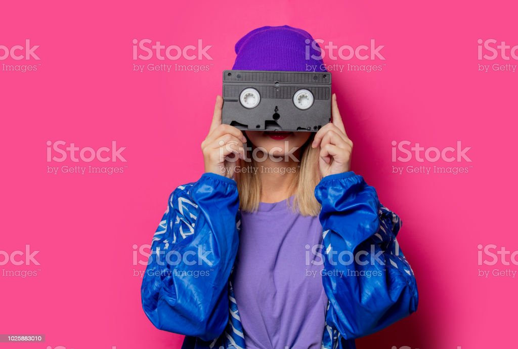 girl in 90s sports jacket and VHS cassette stock photo