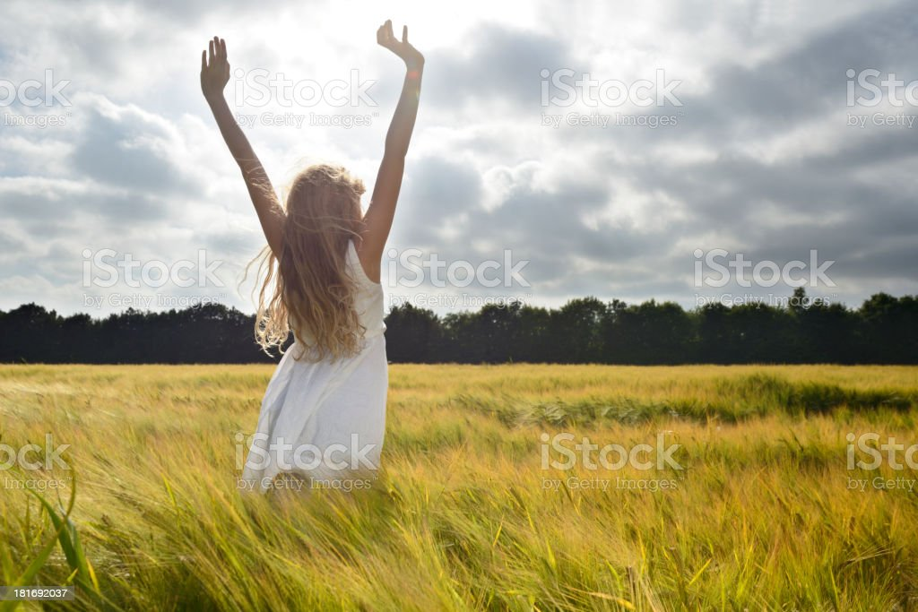 Girl in a barley field in summer, arms outstretched royalty-free stock photo