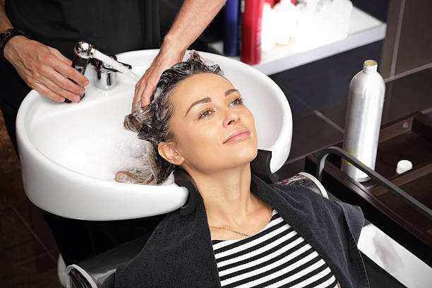 Girl in a beauty salon relaxes a hairdresser's hands wash the head girl in a beauty salon highlights hair stock pictures, royalty-free photos & images