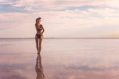 istock A girl in a black swimsuit on the background of the salty sea of the lake. girl a reflection in the water. Woman alone with nature in a swimsuit. model looks into the distance. The view from back 1238586607