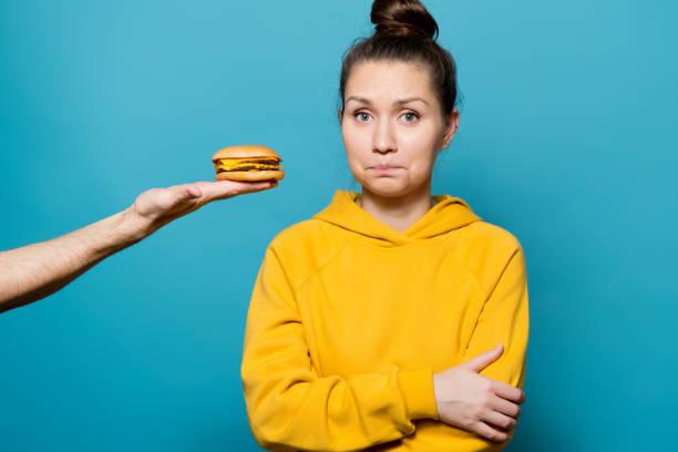 chica en una sudadera brillante con dificultad limita la tentación de probar una hamburguesa - foto de stock