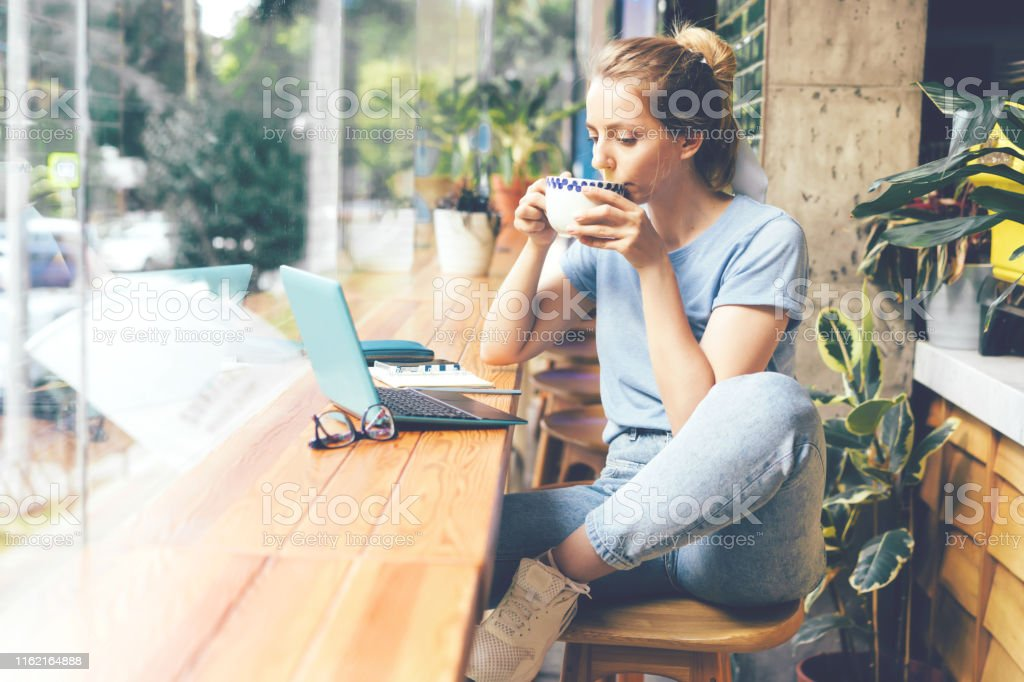 Girl in a cafe with a laptop A young girl sits at the tables at the window in a cafe with a laptop, drinks matcha tea from a large mug and looks at the monitor. 20-29 Years Stock Photo