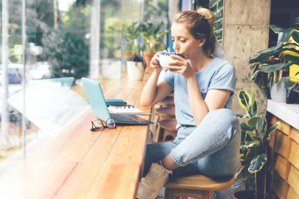 menina em um café com um portátil - working in café - fotografias e filmes do acervo