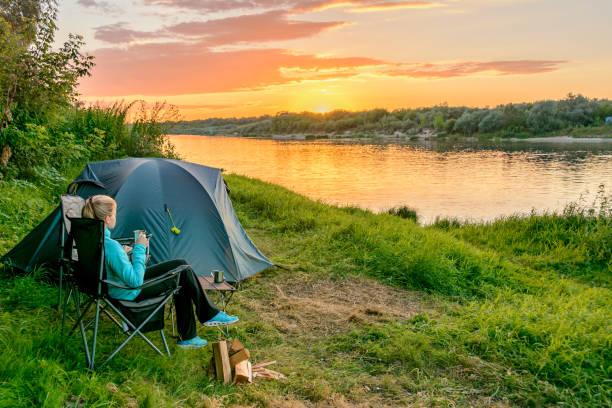 Ein Mädchen auf einem Campingplatz mit einem Touristen-Zelt am Ufer Flusses. Russland. – Foto