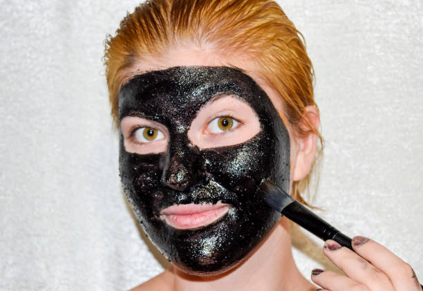Girl in a cosmetic black mask. Cleansing mask of aspirin and activated carbon. Black cosmetic face mask. stock photo