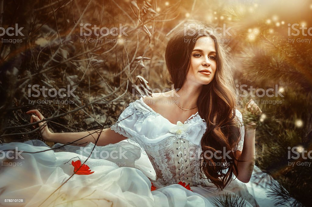 girl in a dress sitting in the woods girl in white dress sitting in forest smiling Adult Stock Photo