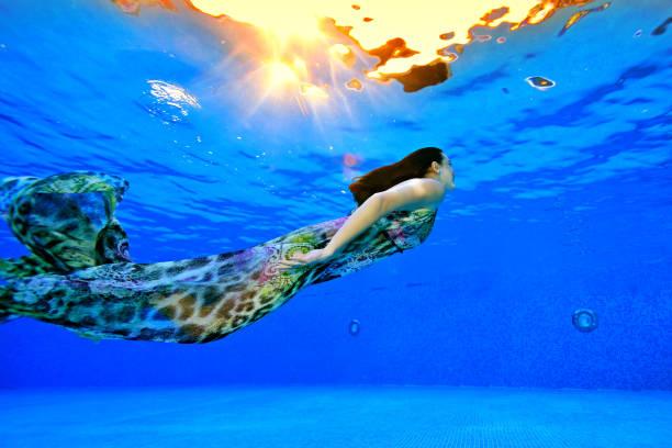 une fille dans une robe nage sous l'eau du fond de la piscine à la surface à la lumière du soleil. tir sous l'eau. vue latérale. orientation horizontale de la photo - défilé de mode photos et images de collection