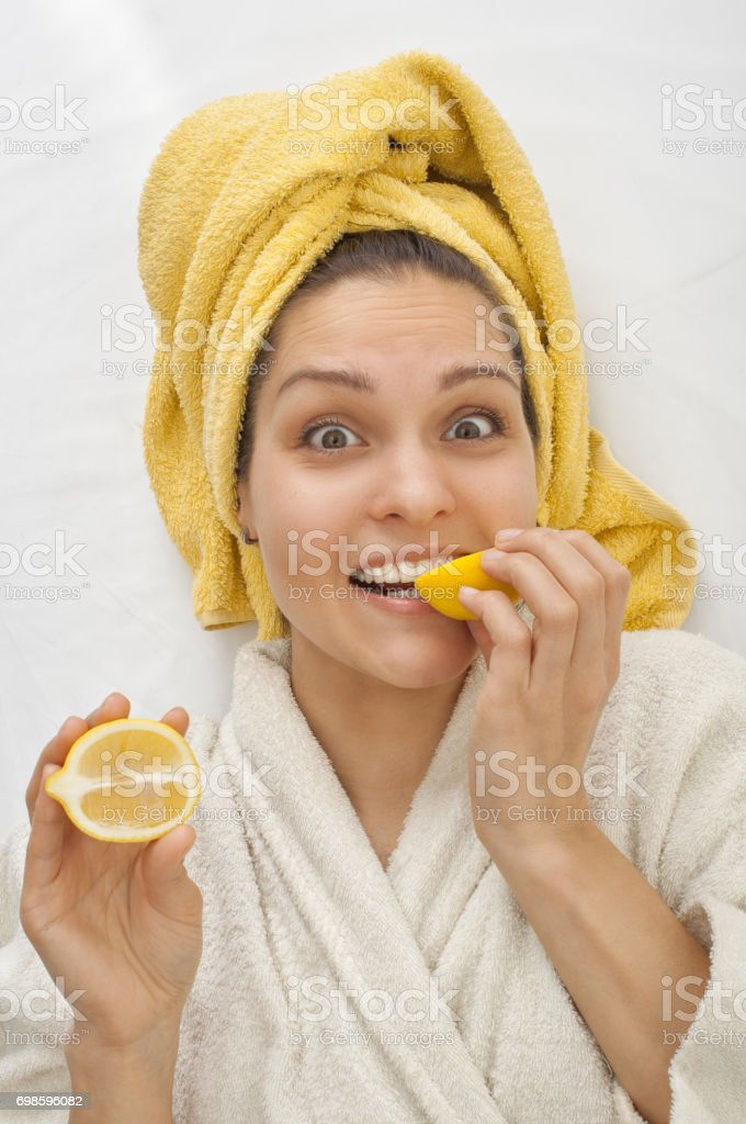 Girl In A Dressing Gown Bites A Lemon Stock Photo & More Pictures of ...