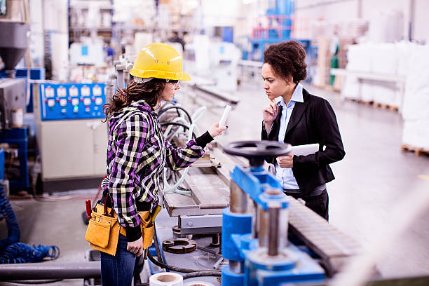 Girl in a factory working with her woman boss stock photo