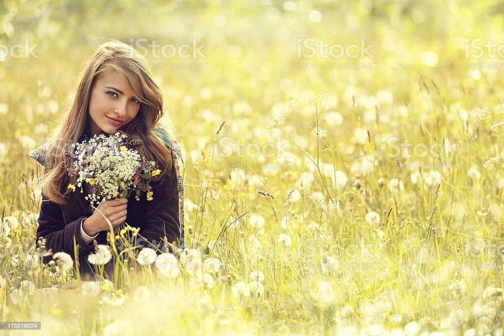 girl in a flower covered field royalty-free stock photo
