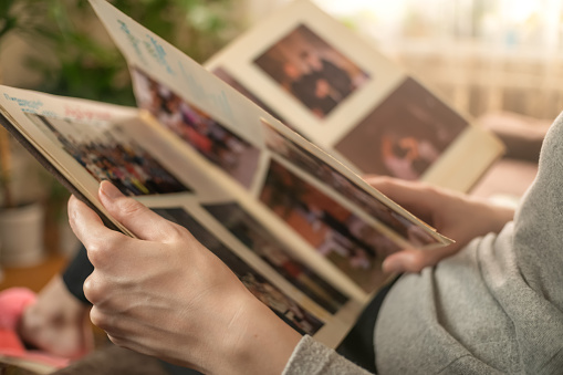 girl in a gray jacket is sitting on the sofa and looking at old photos in a photo album