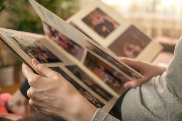 gadis dengan jaket abu-abu duduk di sofa dan melihat foto-foto lama dalam album foto - album potret stok, foto, & gambar bebas royalti