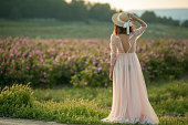 Girl in a hat and a beige dress look at cvvetov field. Photo in full growth