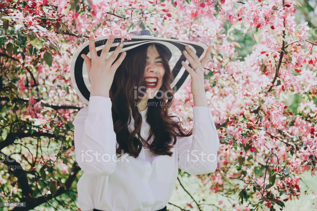 Girl in a hat in blossoming trees. stock photo