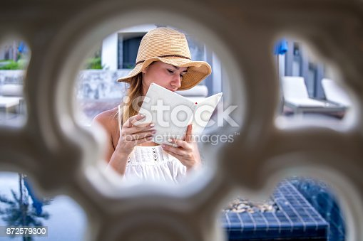 817409212 istock photo girl in a hat reading a book on holiday 872579300