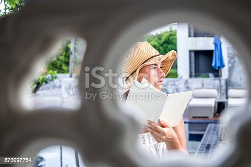817409212 istock photo girl in a hat reading a book on holiday 873697754