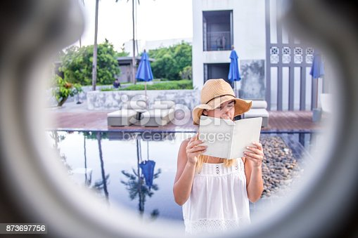 817409212 istock photo girl in a hat reading a book on holiday 873697756