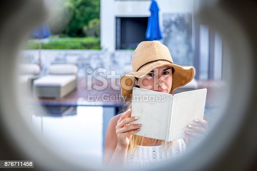 817409212 istock photo girl in a hat reading a book on holiday 876711458