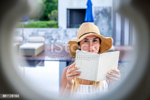 817409212 istock photo girl in a hat reading a book on holiday 881128164