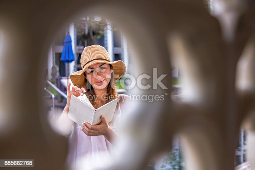 817409212 istock photo girl in a hat reading a book on holiday 885662768