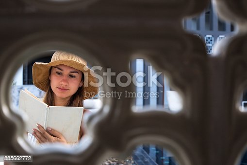 817409212 istock photo girl in a hat reading a book on holiday 885662772
