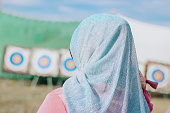 A girl in a hijab against the background of targets for archery and arbalest. Muslim woman in a blue shawl. Hit the target. Targets.