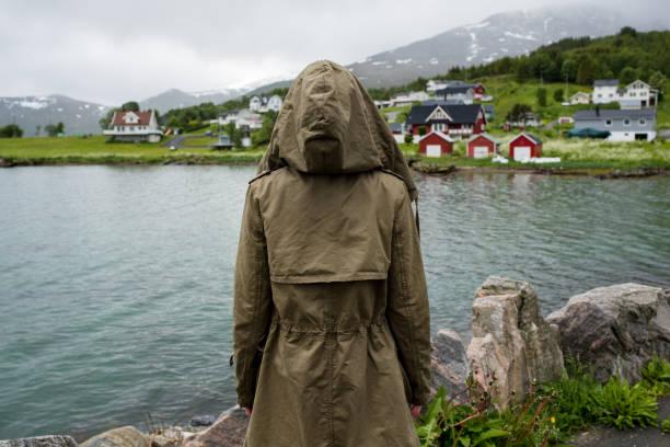 ein mädchen in jacke schaut auf eine stadt. erkunden sie norwegen. schöne landschaft im norden. ozean und berg. erstaunliche malerische aussicht auf die natur. architektur, skandinavischer stil. genießen sie den moment, entspannung. reisen, abenteuer, l - dorfkind momente stock-fotos und bilder